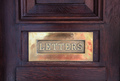Brass mail letter box on a wooden front door, text letters - PhotoDune Item for Sale