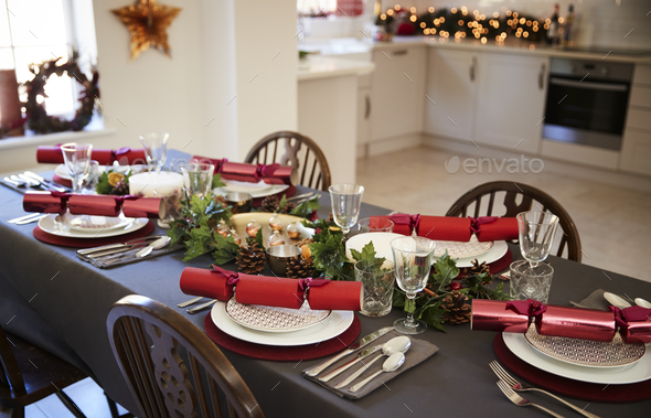 Christmas table setting with Christmas crackers arranged on plates  - Stock Photo - Images
