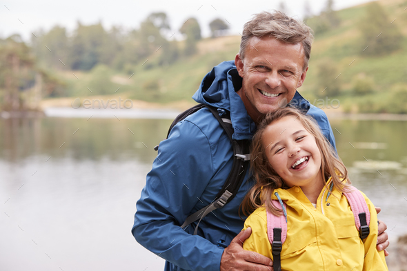 Caucasian pre-teen girl standing with her father on the shore of a lake - Stock Photo - Images