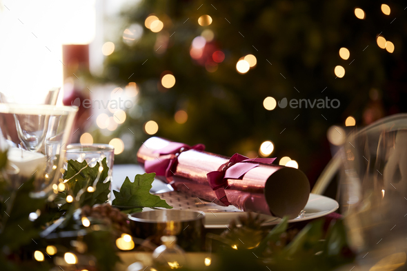 Close up of Christmas table setting with a Christmas cracker arranged on a plate  - Stock Photo - Images