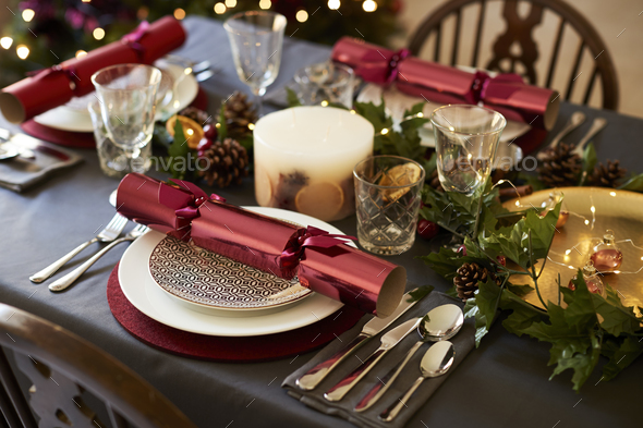 Close up of Christmas table setting with Christmas crackers arranged on plates  - Stock Photo - Images