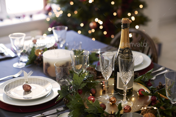 Christmas table setting with glasses and a bottle of champagne - Stock Photo - Images