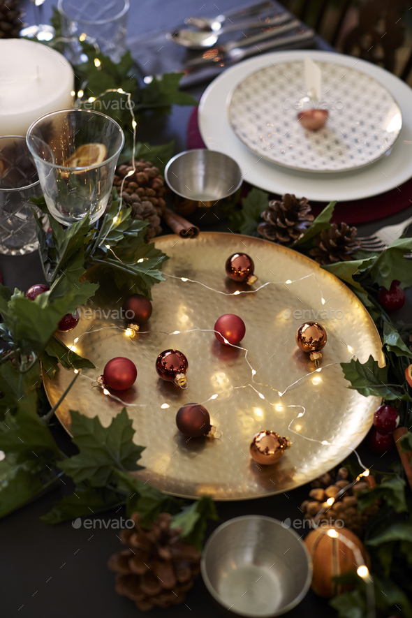 Christmas table setting with baubles on golden plate, bauble name card holder  - Stock Photo - Images