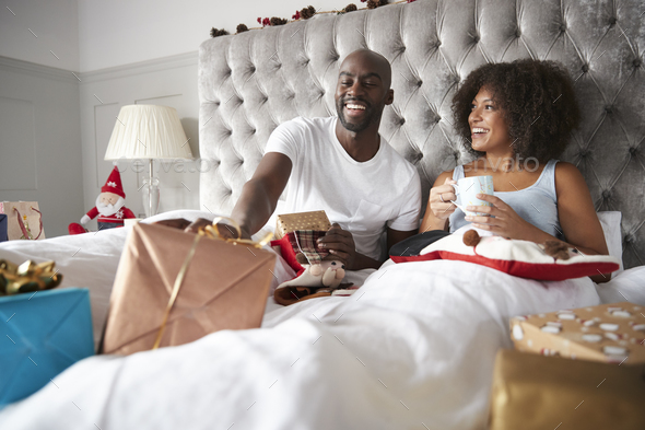 Happy young black couple sitting in bed giving gifts to each other on Christmas morning, low angle - Stock Photo - Images
