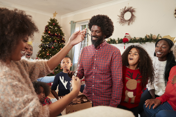 Couple Exchanging Gifts As Multi Generation Family Celebrate Christmas At Home Together - Stock Photo - Images