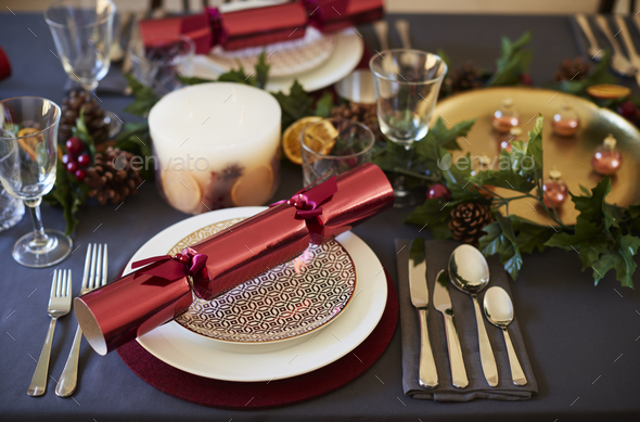Close up of Christmas table setting with crackers arranged on plates  - Stock Photo - Images