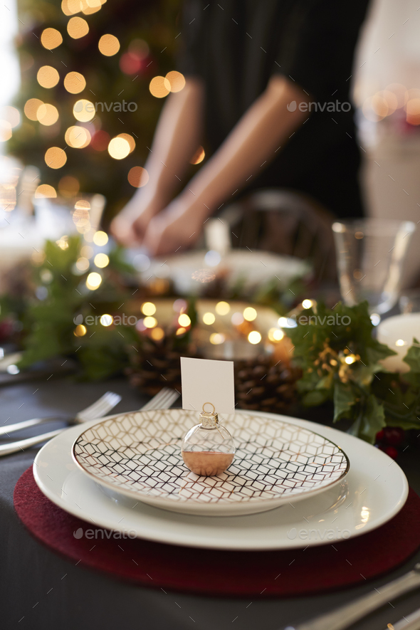 Christmas table setting with bauble name card holder arranged on a plate - Stock Photo - Images
