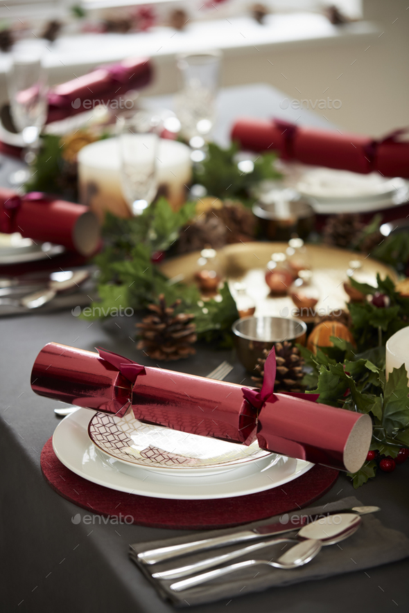 Close up of decorated Christmas table setting, with centrepiece and Christmas crackers  - Stock Photo - Images
