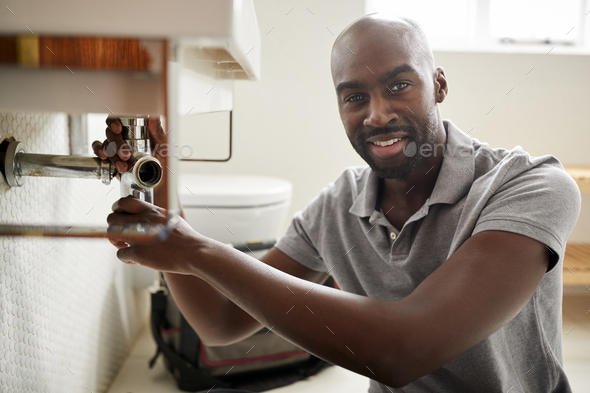Young black male plumber sitting on the floor fixing a bathroom sink, looking to camera, close up - Stock Photo - Images