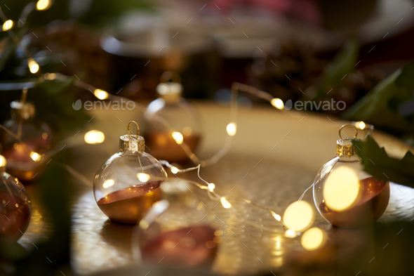 Close up of Christmas baubles on a gold table with warm glow, selective focus - Stock Photo - Images