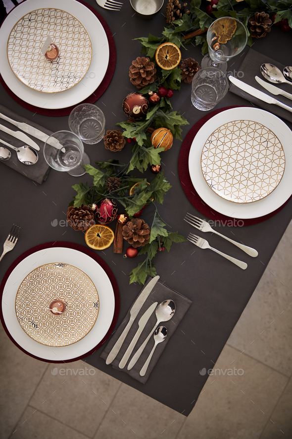 Christmas table setting with baubles arranged on plates  - Stock Photo - Images