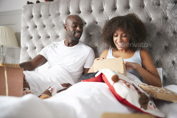 Young adult black couple opening gifts in bed on Christmas morning, low angle - Stock Photo - Images