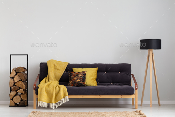 Log of wood next to comfortable sofa with yellow blanket and pil
