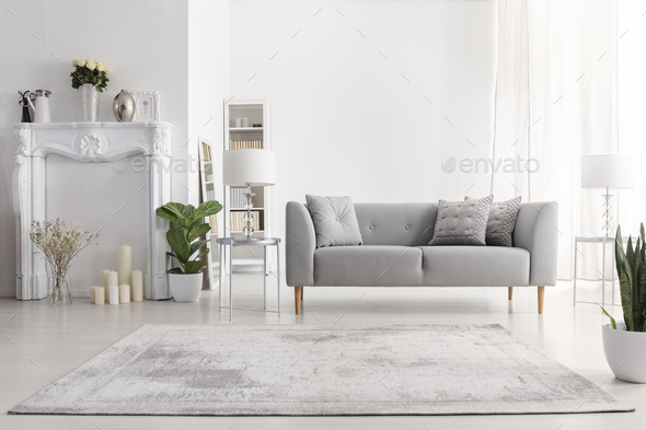 Plants and carpet in white living room interior with candles nex