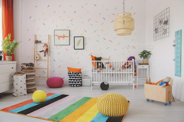 Poufs on colorful rug in scandi baby's room interior with cradle - Stock Photo - Images