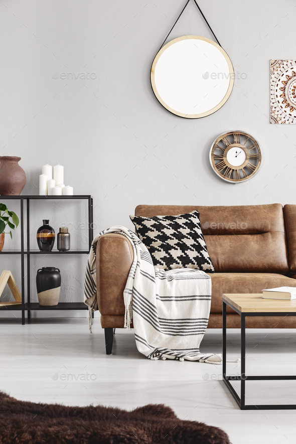 Vertical view of warm ethno living room with leather couch with - Stock Photo - Images