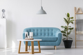 White wooden coffee table next to blue elegant couch in bright l - PhotoDune Item for Sale