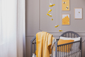 Yellow blanket on grey wooden crib in bright baby bedroom with y - PhotoDune Item for Sale