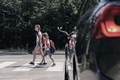 Low angle on car in front of children with backpacks walking thr - PhotoDune Item for Sale
