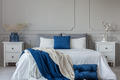 King size bed with grey, blue and white bedding between two wood - PhotoDune Item for Sale