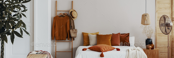 Pillow on a bed next to a ladder with hanging jumpers in a natur - Stock Photo - Images