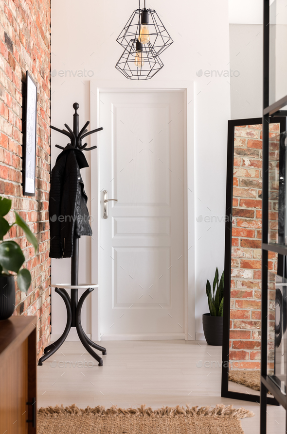 White and brick walled entrance hall interior in real photo with - Stock Photo - Images