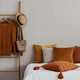 Pillow on a bed next to a ladder with hanging jumpers in a natur - PhotoDune Item for Sale