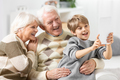 Smiling grandson taking selfie of himself and his happy grandpar - PhotoDune Item for Sale