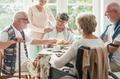Happy seniors having a cake in a nursing home - PhotoDune Item for Sale