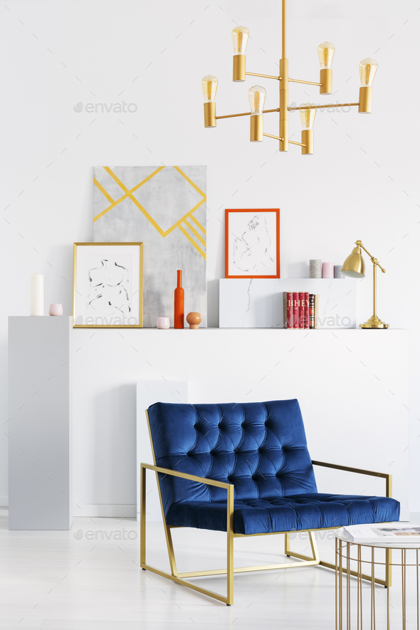 Gold lamp above blue armchair in white living room interior with - Stock Photo - Images