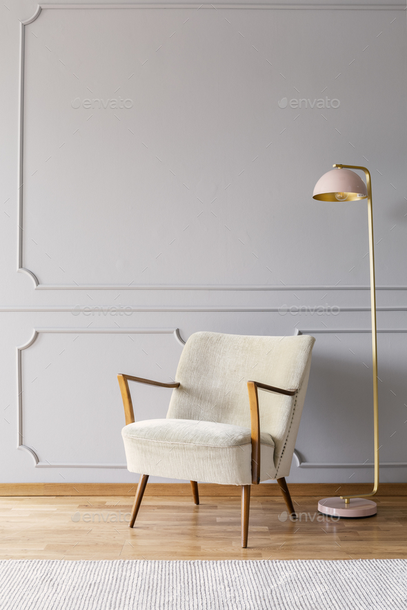 Real photo of pastel pink metal lamp standing by the white armch - Stock Photo - Images