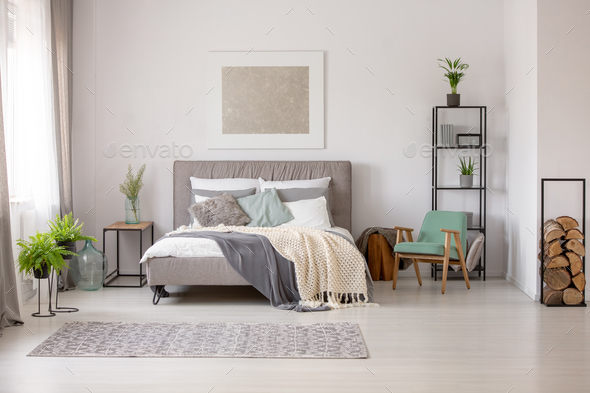Knitted blanket on grey bed in bright bedroom interior with gree - Stock Photo - Images