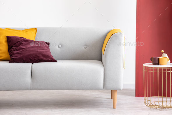 Purple and orange cushion on grey sofa next to table in grey and