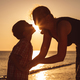 Mother and son playing on the beach at the sunset time. - PhotoDune Item for Sale