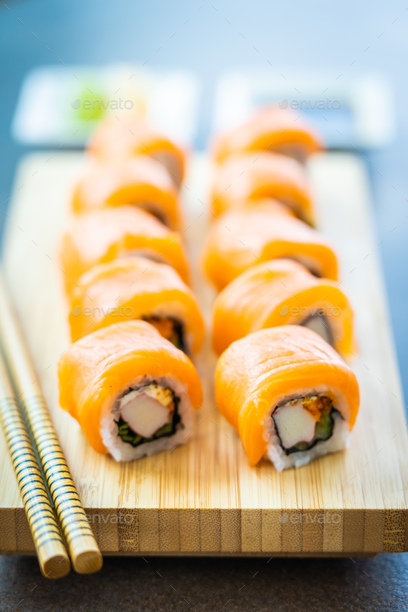 Salmon fish meat sushi roll maki on wood plate - Stock Photo - Images