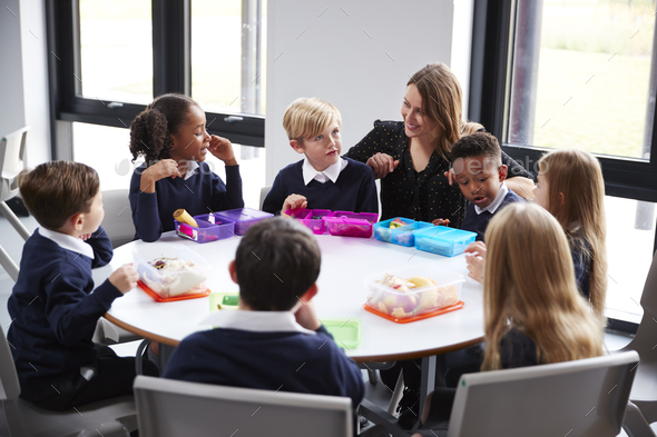 Teacher kneeling to talk to a group of primary school kids sitting eating their packed lunches - Stock Photo - Images