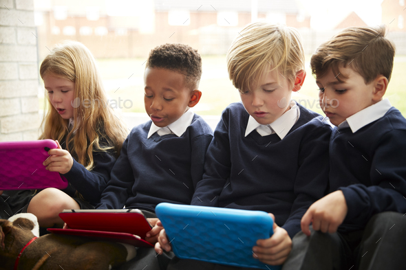 Four primary school children sitting on the floor in front of a window using tablet computers  - Stock Photo - Images