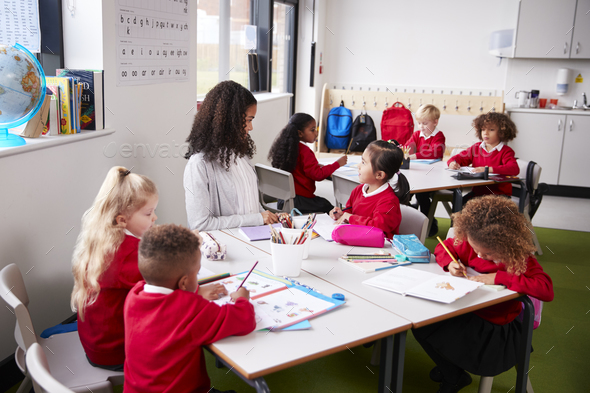Young female infant school teacher sitting at a table in a classroom with her pupils - Stock Photo - Images