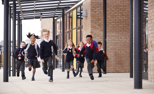 Primary school kids, wearing school uniforms and backpacks, running on a walkway  - Stock Photo - Images