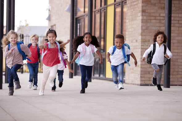 Smiling multi-ethnic school kids running in a walkway outside their infant school building  - Stock Photo - Images