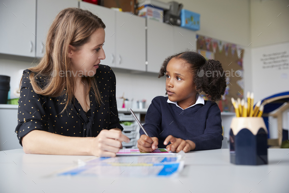 Young female primary school teacher working one on one with a schoolgirl at a table in a classroom - Stock Photo - Images