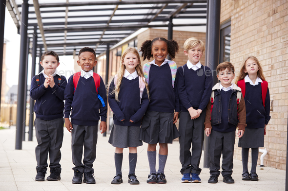 Primary school kids standing in a row on a walkway outside their school, smiling to camera - Stock Photo - Images
