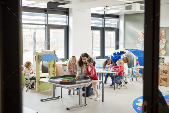 Kids playing games with a female teacher in a classroom in an infant school, seen from doorway - Stock Photo - Images