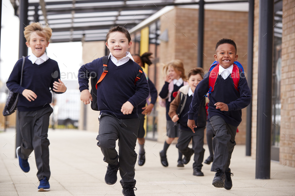 Excited primary school kids  running on a walkway outside their school building - Stock Photo - Images