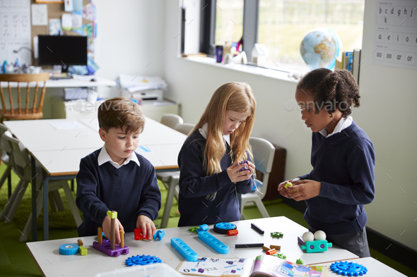 Elevated view of three primary school kids working together using construction blocks in a classroom - Stock Photo - Images