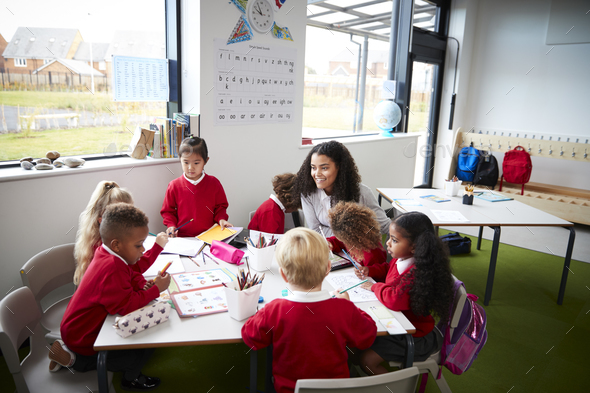 A group of infant school kids sitting at a table in a classroom with their female teacher - Stock Photo - Images