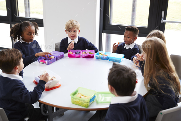 Elevated view of primary school kids sitting together at a round table eating their packed lunches - Stock Photo - Images