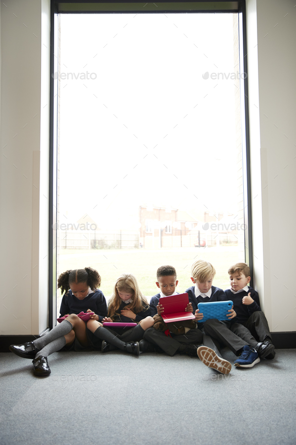 Primary school kids sitting in front of a window in a school corridor using tablet computers - Stock Photo - Images