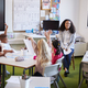 Young female infant school teacher sitting on a chair facing school kids in a classroom - PhotoDune Item for Sale