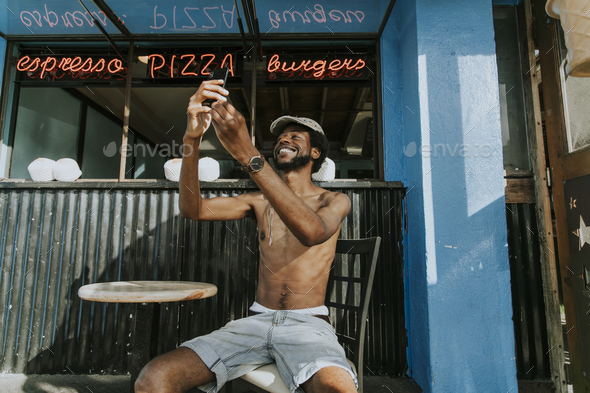 Shirtless man sitting at a cafe - Stock Photo - Images